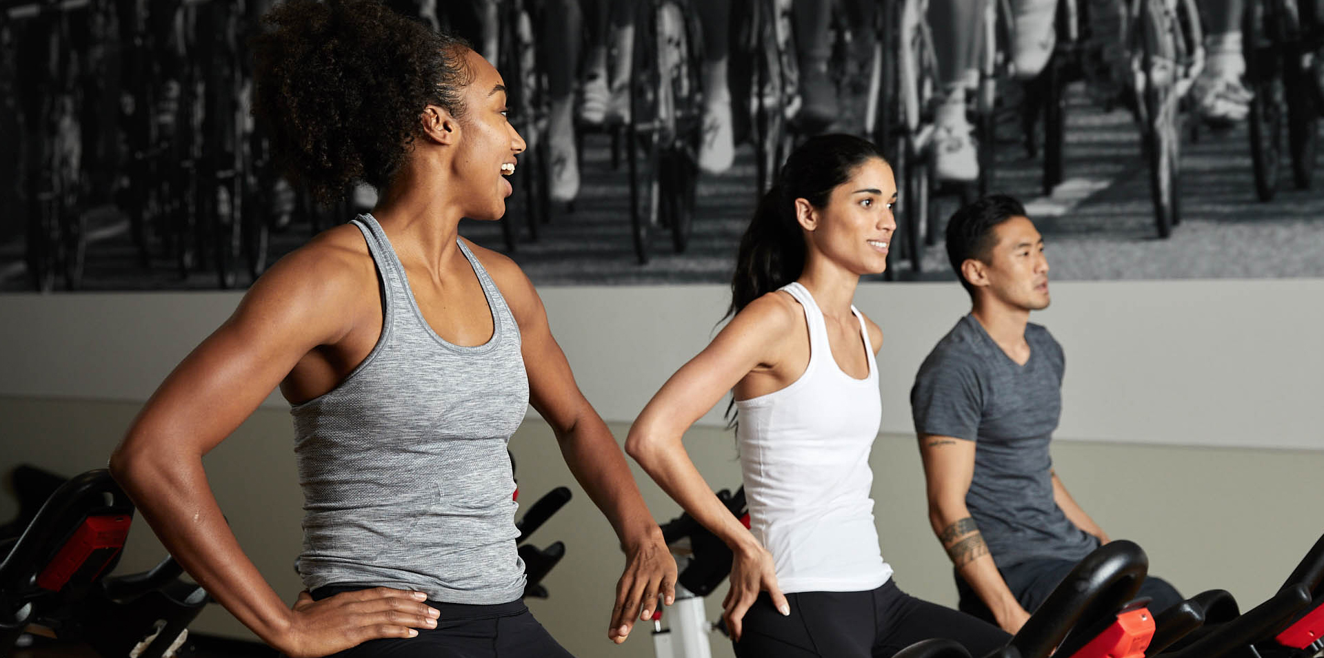 Three members in a cycling group fitness class