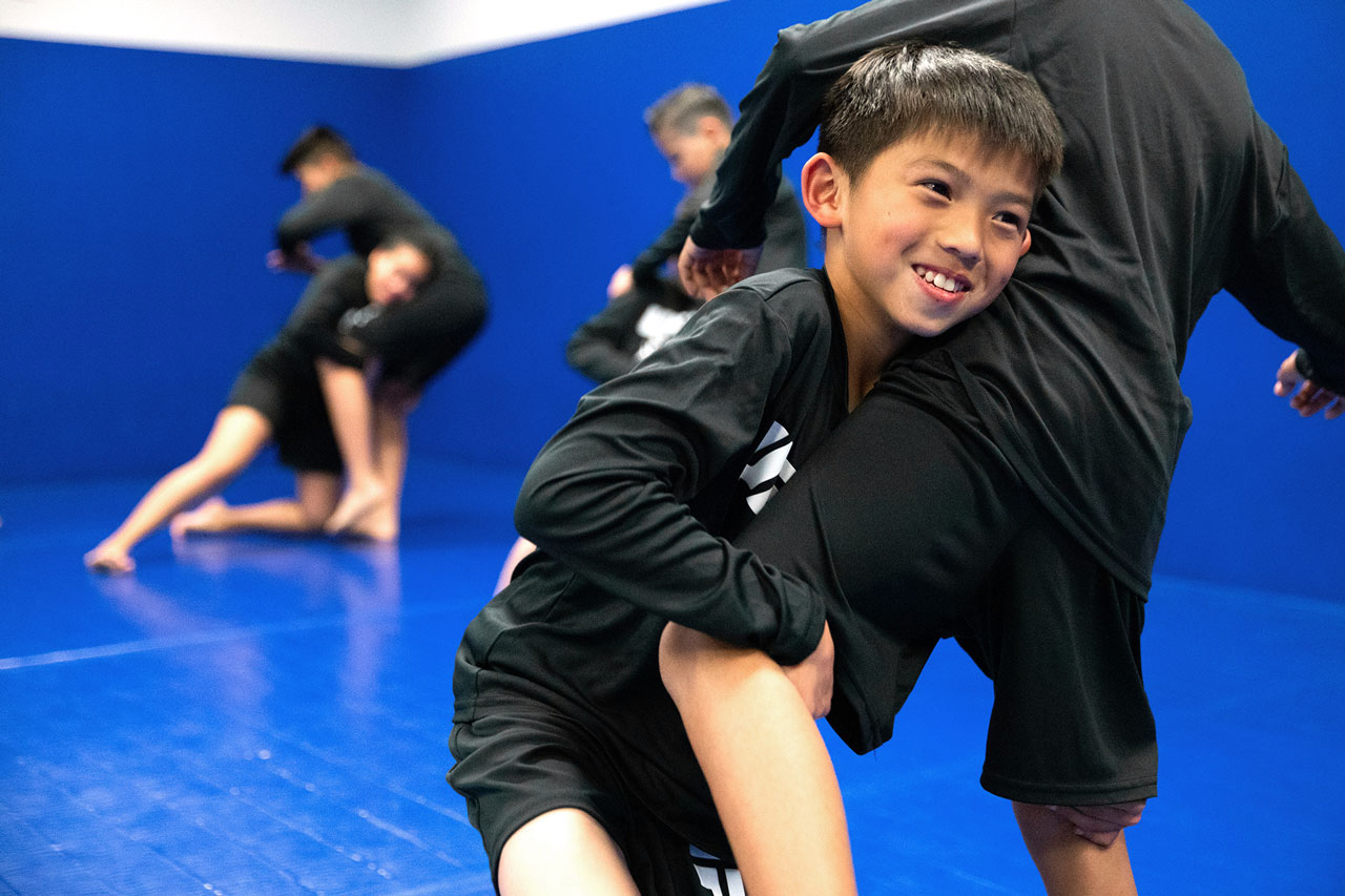 Young members practicing brazilian jiu jitsu
